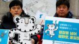 Coreanos posan junto a la mascota de los JO de Invierno