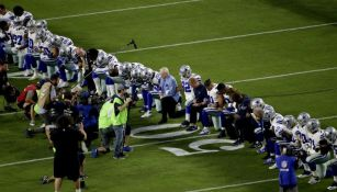 Dallas Cowboys se hincan frente a la bandera de E.U.