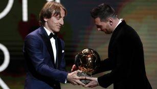 Luka Modric dando el Balón de Oro a Lionel Messi