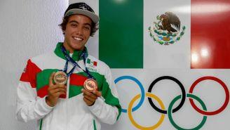 Jhony Corzo sostiene sus medallas junto a los aros olímpicos