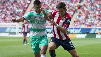 Osvaldo Martínez y Carlos Fierro disputan un balón en un partido entre Chivas y Santos
