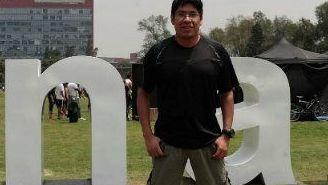 Marco A. Zaragoza posa frente a las iniciales de su universidad