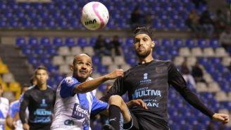 Edgar Lugo disputa un balón en el juego contra Puebla