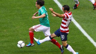 Landon Donovan intenta detener la jugada de Andrés Guardado