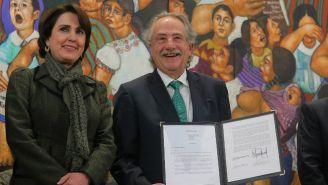 Decio de María muestra un documento junto a Patricia Mercado