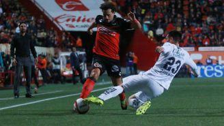 Matías Aguirregaray conduce el balón pese a recibir una barrida de Juan Cornejo