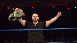 Austin Aries festeja con el cetro de IMPACT wrestling en el ring