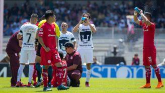 Jugadores de Pumas y Toluca hidratándose en la cancha de CU