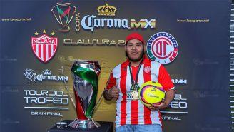 Aficionado de los Rayos posa junto al trofeo de la Copa MX