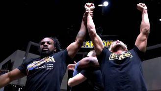 Xavier Woods levanta los brazos de Kenny Omega tras el combate