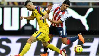 Guido Rodriguez y Alan Pulido disputan el balón en el Clásico Nacional
