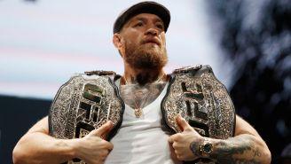 Conoi McGregor posa con sus dos campeonatos de la UFC