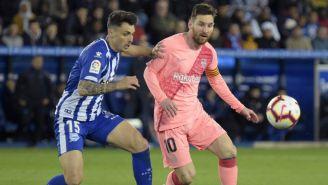 Messi intenta quedarse con el balón ante la persecución de un defensa