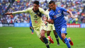 Edson Alvarez y Roberto Alvarado pelean un balón