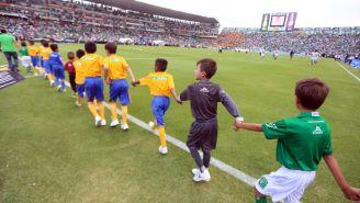 Niños saltan al terreno de juego durante el protocolo