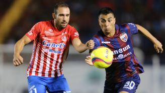 Alejandro Catro y Diego Cardozo disputan un balón