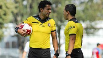 Luis Alfredo García y su asistente debaten una jugada
