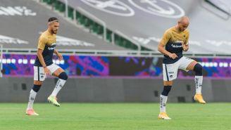 Nicolás Freire y Carlos González en calentamiento con Pumas en el Apertura 2020