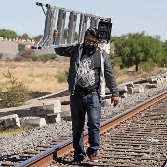 Aficionado del América camina por las vías del tren con una escalera