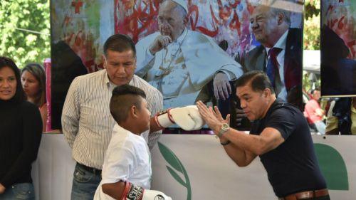 Chiquita González le muestra a un pequeño las técnicas de boxeo