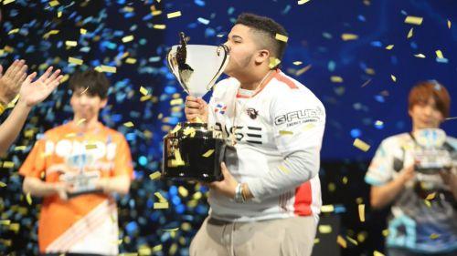 MenaRD besa la copa que lo acredita como el mejor jugador de Street Fighter V
