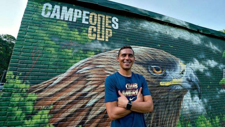 Paul Aguilar posa junto a un mural de la cancha rehabilitad