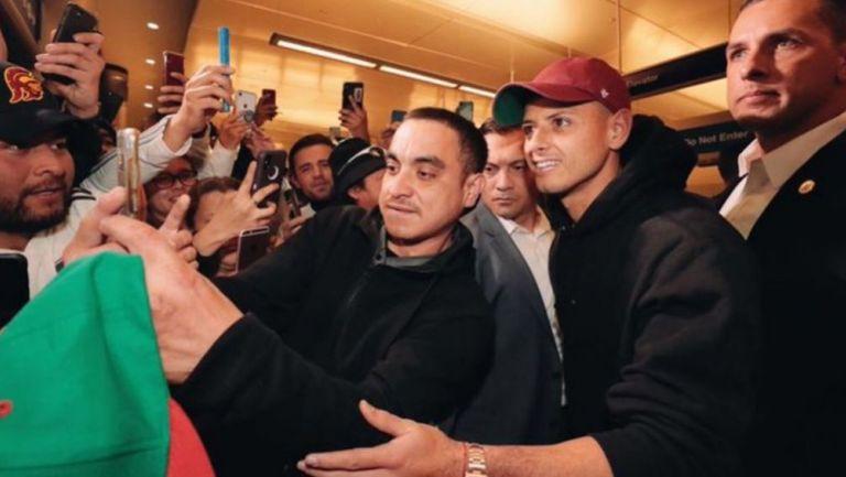 Chicharito posa con un aficionado a su llegada a Los Angeles